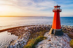 Red lighthouse on the rocky seashore