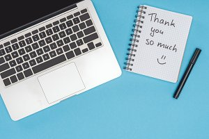 laptop, pen and notebook with thank