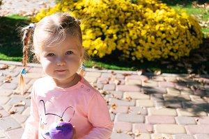 Little girl standing near plants in