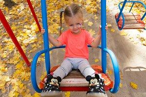 Little girl swinging on swing in the