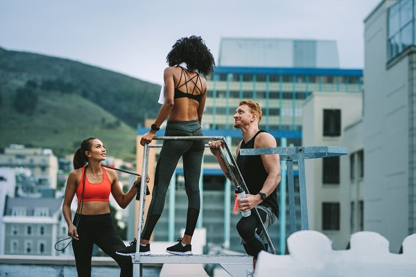 Fitness colleagues standing on roof