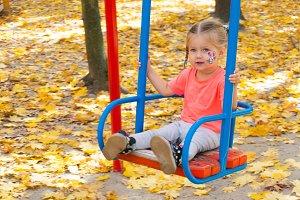 Girl swinging on swing in autumn