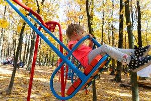 Girl swinging on swing in kids park