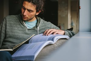 Man writing in book sitting at home