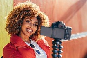 Smiling female blogger shooting