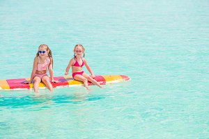 Little girls swimming on surfboard d