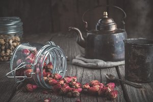 Teapot, cup of herbal tea, dry roses