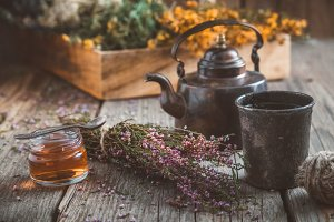 Teapot, tea cup, honey jar and herbs