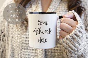 Woman holdin mug with black handle