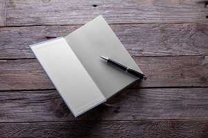 Blank open book with pen.