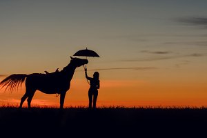 Horse girl with umbrella on sunset