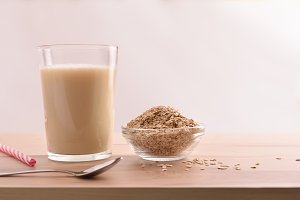 Oat drink in glass isolated front