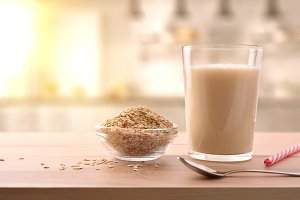 Oat drink in glass and cereal flakes