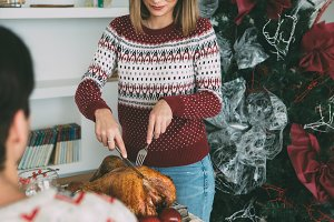 Young woman carves the turkey at Chr