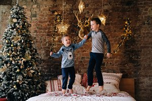 Happy kids jumping on bed