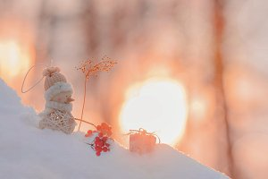 Snowman with gifts at sunset