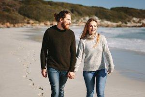 Smiling couple walking on beach