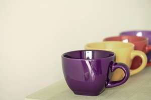 row of colorful cups on wooden table