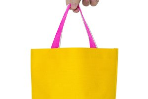 hand holding yellow fabric bag