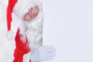 Santa Claus peeking from behind sign
