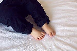 legs of the baby in black pants