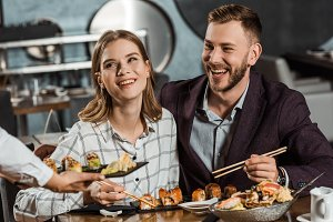 Smiling couple eating sushi rolls wh