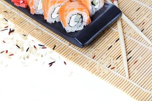 Fresh salmon sushi rolls on wooden b