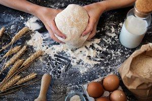 Knead the dough with wheat on dark b