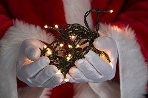 santa claus hand with christmas ligh