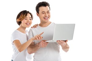 smiling young couple using laptop is