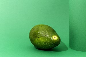 Fresh avocado on green background