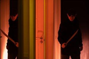 Photo of thief with machete in dark