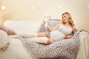 Happy pregnant woman relax on a sofa