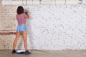 young attractive woman paints white