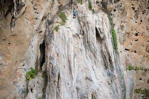 Young man rock climbing on karst lim