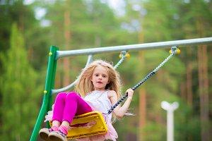 Little blonde girl smiling swinging