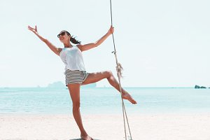 Young woman on swings on sea beach