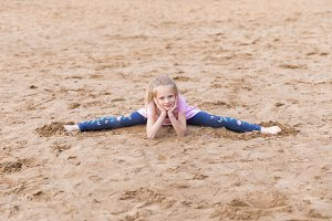 Little blonde girl stretches on sand