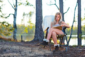 Young blonde woman in camping near l
