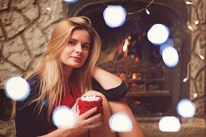 Pretty blonde woman near fireplace w