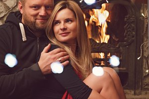 Pretty couple near fireplace ready f