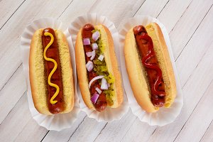 Three hot dogs on a wood table