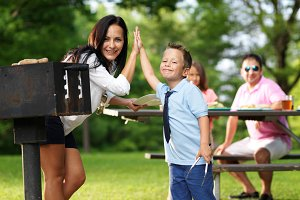 mother and son high five at picnic