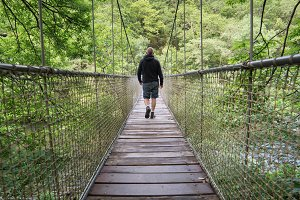 Man crossing a suspension bridge