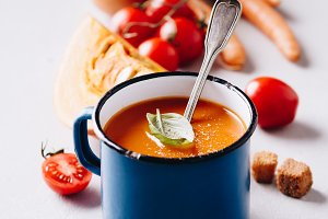 Old metal cup of tomato soup on conc