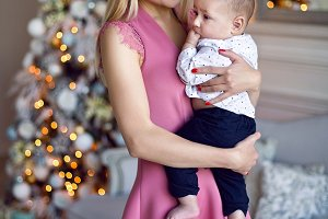woman in a pink dress holds her son