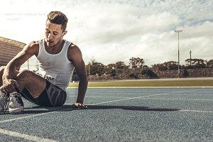 Runner sitting on running track hold