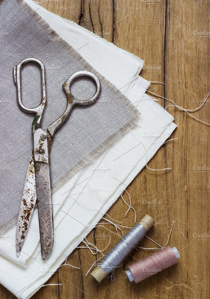 Sewing kit. Scissors, bobbins with thread and needles on the old wooden background - Arts & Entertainment