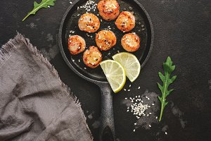 Fried scallops in a frying pan, dark