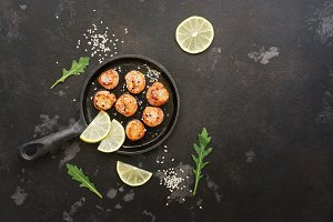 Scallops fried in a pan with lemon